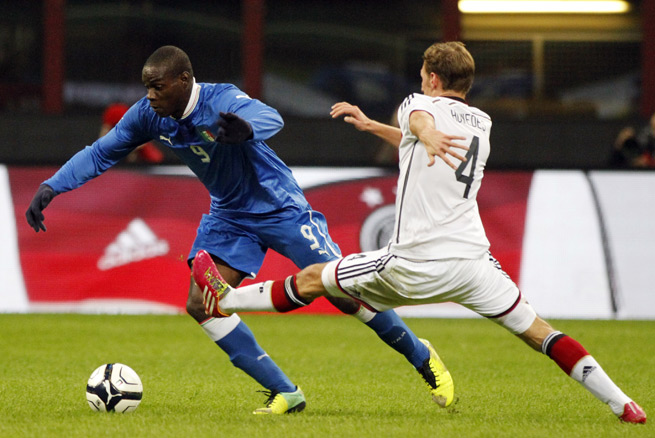 Italy's Mario Balotelli looks to get by Germany's Benedikt Howedes in the two European powers' 1-1 draw in Milan Friday.