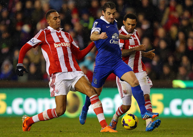 Everton's Leighton Baines, center, played hero for the Toffees, netting a second-half, stoppage-time penalty to rescue a point at Stoke City.