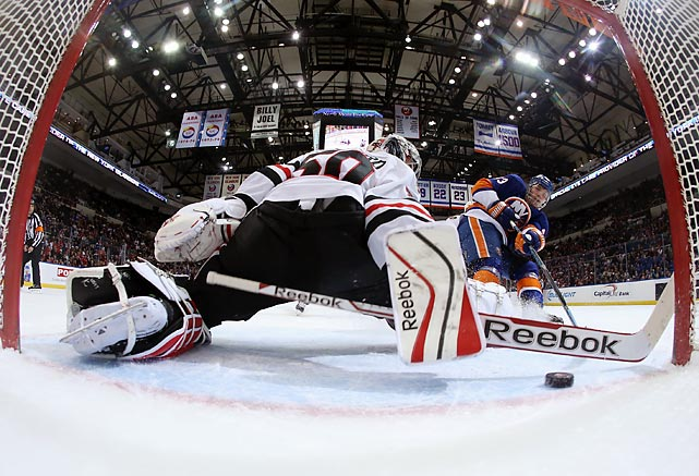Casey Cizikas of the New York Islanders slides the puck past Chicago's Corey Crawford for an early goal during a Thursday game. One of the worst teams in the league, the Islanders earned an 3-2 overtime victory over the Blackhawks, one of the NHL's best teams.