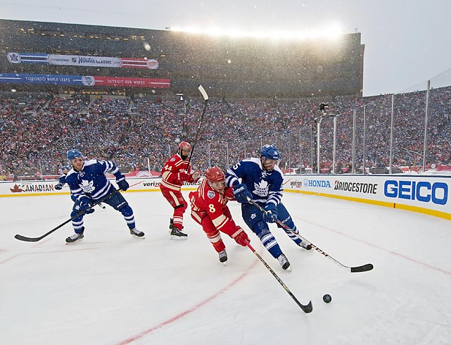 Detroit Red Wings forward Justin Abdelkader and Toronto Maple Leafs defenseman Paul Ranger reach for the puck during this season's Winter Classic. The game, played in snowy conditions at Michigan Stadium in Ann Arbor, ended in a 3-2 shootout victory for Toronto.