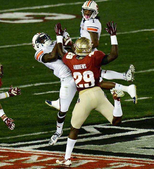 Florida State defensive back Nate Andrews tries to defend a pass in the hands of a falling Auburn receiver.