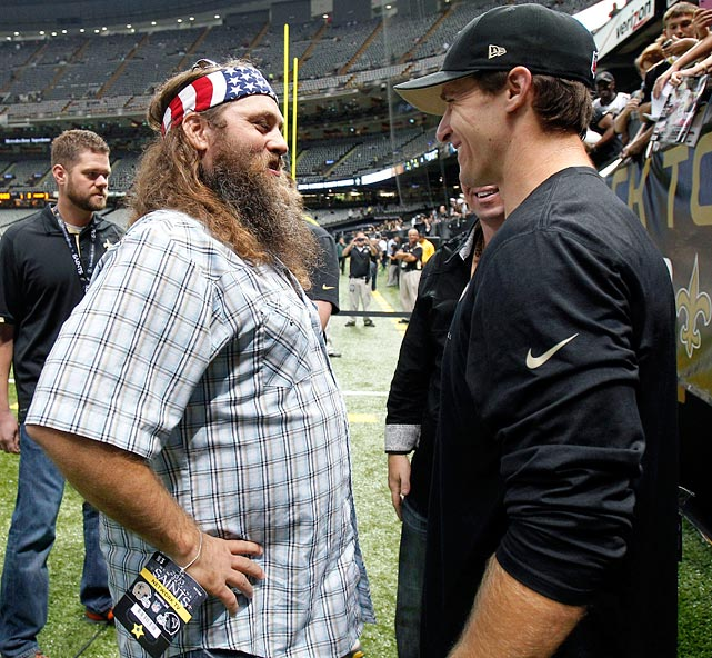 """Duck Dynasty"" star Willie Robertson chats with Brees on the field before an the Saints games against the Atlanta Falcons in New Orleans on Sept. 8, 2013."