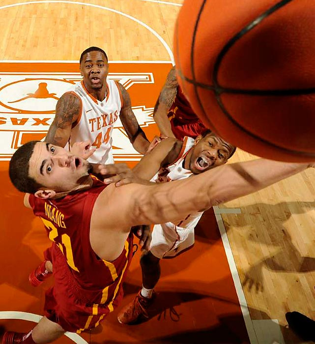Iowa State forward Georges Niang maneuvers around several Texas defenders with the ball. The Longhorns ultimately won the game 86-76 despite 18 points from Niang for the No. 8 Cyclones.