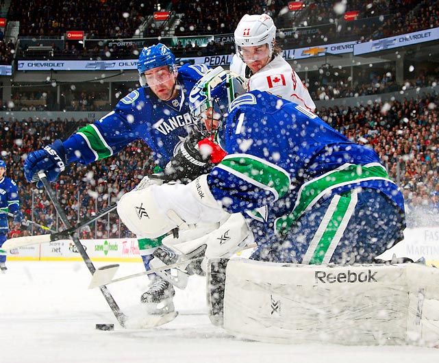 Vancouver Canucks goaltender Roberto Luongo reaches to stop the puck in a Saturday game against the Calgary Flames. Vancouver topped Calgary 3-2 in a shootout, with Luongo notching 31 saves.