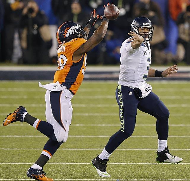 Russell Wilson flips a pass to avoid being sacked by outside linebacker Danny Trevathan. Seattle did allow a sack all night.