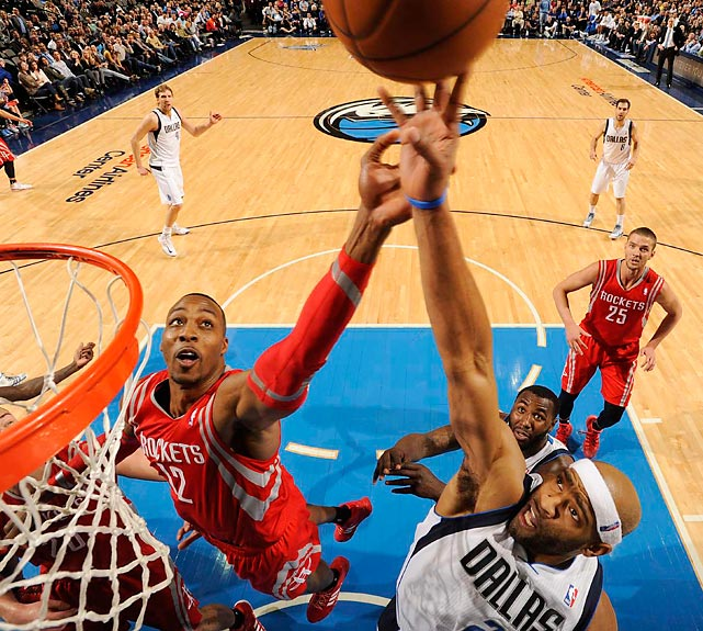 Vince Carter of the Dallas Mavericks tries to tip the ball into the net as Houston Rockets center Dwight Howard defends. Carter finished with a season-high 22 points in a 117-115 loss to Houston.