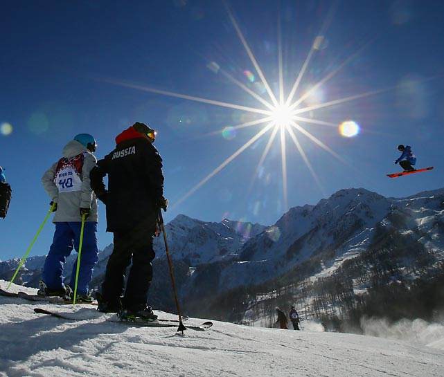 Skiers watch as a rider jumps during a Monday training session for the Ski Slopestyle competition ahead of the Sochi 2014 Winter Olympics.