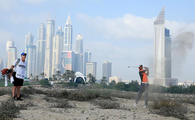 Tiger Woods attempts a shot from the desert sand during the third round of the 2014 Omega Dubai Desert Classic in Dubai. Woods finished tied for 41st, his worst finish ever in the event.