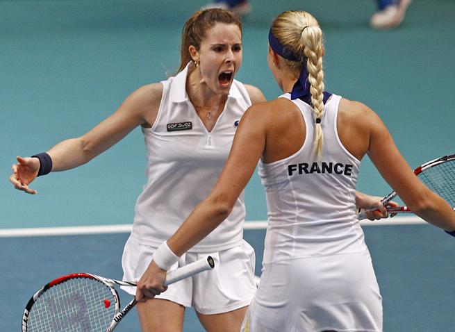 Alize Cornet and Kristina Mladenovic celebrate a set win in a doubles match vs. Switzerland.