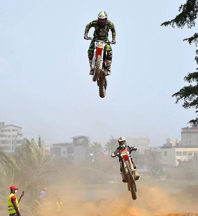 Senior riders jump while competing in the 2014 National Motocross Championships in Abidjan, Ivory Coast.