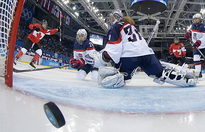 USA goalie Jessie Vetter looks back at the winning goal by Canada's Meghan Agosta-Marciano (left).