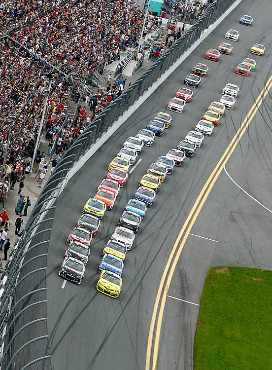 Austin Dillon and Matt Kenseth lead the field to the green flag to start the NASCAR Sprint Cup Series Daytona 500. The race was temporarily halted early due to heavy rain.