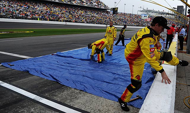 Crew members for David Gilliland place tarps over his pit.