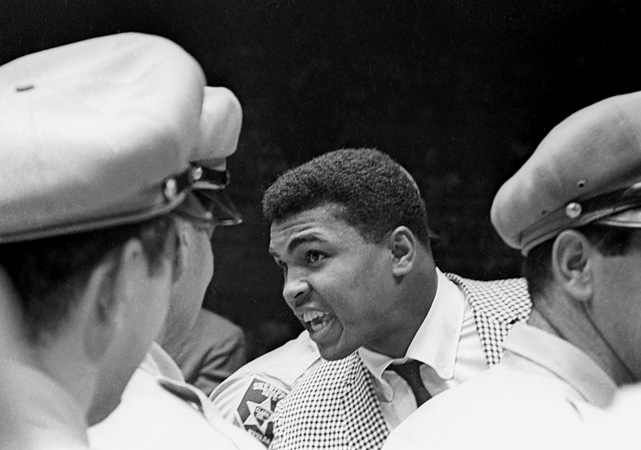 Certainly the loud-mouthed kid from Louisville was not the guy anyone expected to beat Liston. Cassius Clay (later known as Muhammad Ali) had won the light heavyweight gold medal at the Rome Olympics in 1960 and had run up a 19-0 record as a pro. The Louisville Lip, here taunting Liston from ringside after the second Patterson fight, was a master self-promoter, but seemed an unlikely challenger for the champion.