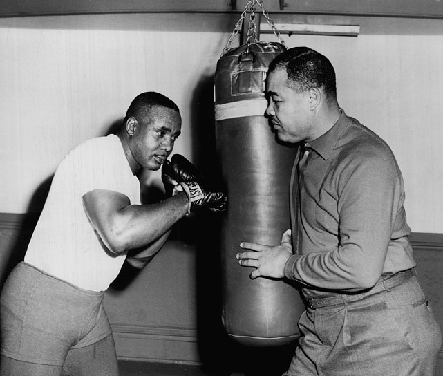 In December of 1963, Liston began training for his bout with Clay, scheduled for February 1964. Here, the reigning champ got some posed help from former heavyweight king Joe Louis.