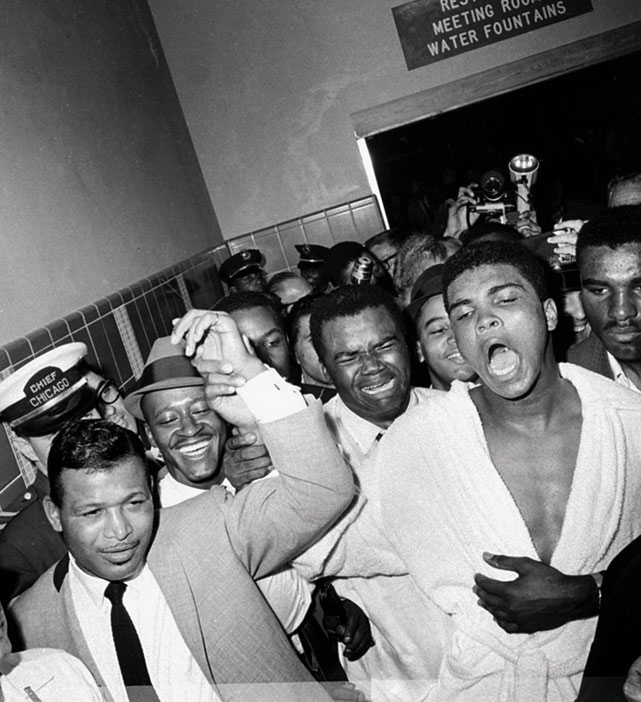 "A sweet moment: Still celebrating and proclaiming himself the ""greatest,"" Clay returned to his dressing room escorted by the great Sugar Ray Robinson (in tie), and trailed by his longtime friend and handler Drew (Bundini) Brown (over Ali's right shoulder)."