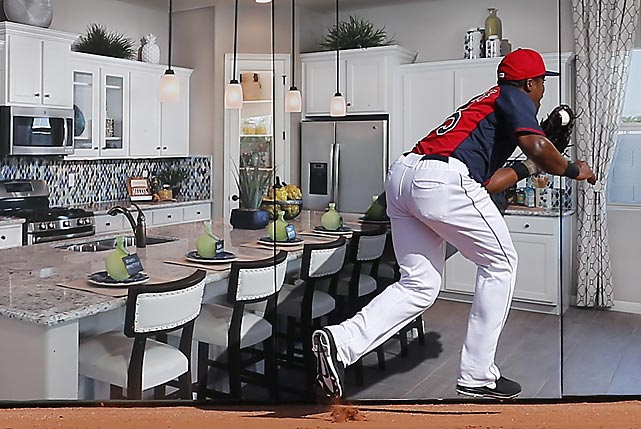 A fastball in Kristopher Negron's kitchen wound up in the glove of Cleveland Indians' right fielder Carlos Moncrief during a Cactus League game against the Red of Cincinnati in Goodyear, Ariz. (That rather arresting wall display is actually an advertisement for a local homebuilder.)