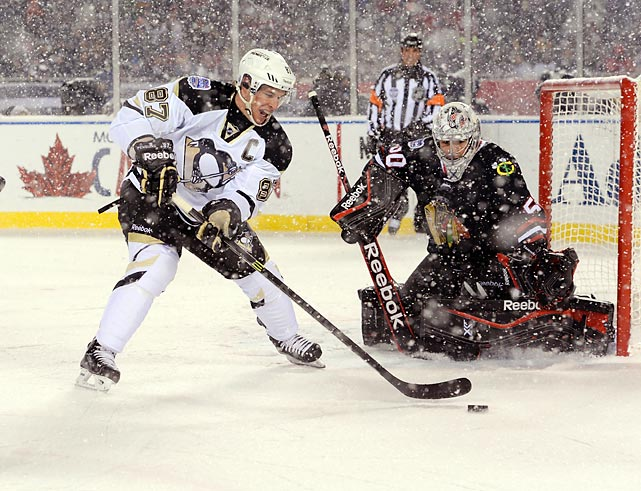 Sidney Crosby of the Pittsburgh Penguins attempts to backhand the puck past Chicago Blackhawks goaltender Corey Crawford during a Saturday night NHL contest at Soldier Field in Chicago. Snow pelted the ice throughout the game -- a 5-1 victory for the Blackhawks -- which was played outdoors as part of the NHL's Stadium Series.