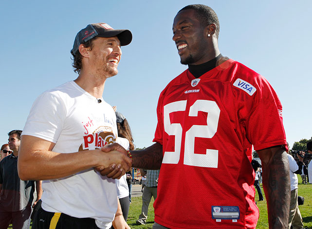 Matthew McConaughey and San Francisco 49ers linebacker Patrick Willis shake hands as they watch football drills at the 49ers Academy School in East Palo Alto, Calf., on Sept. 28, 2010.
