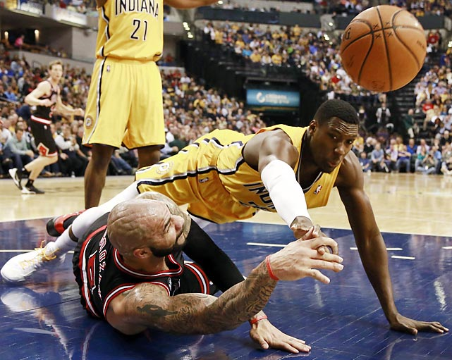 Chicago Bulls forward Carlos Boozer, left, passes as Indiana Pacers center Ian Mahinmi dives for the ball in the first half of their game on Friday.