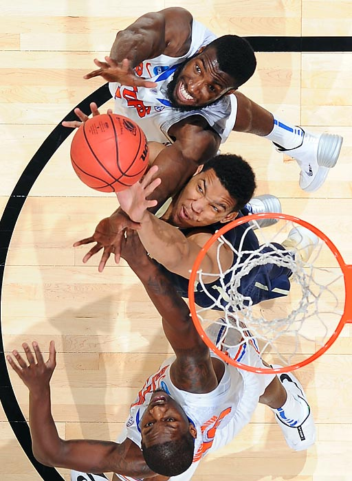Pittsburgh's Derrick Randall attacks the basket defended by Patric Young (4) and Dorian Finney-Smith (10) of Florida during the third round of the 2014 NCAA Men's Basketball Tournament.