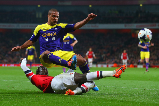 Arsenal's Bacary Sagna upends Swansea's Wayne Routledge while making the tackle in Tuesday's 2-2 draw.