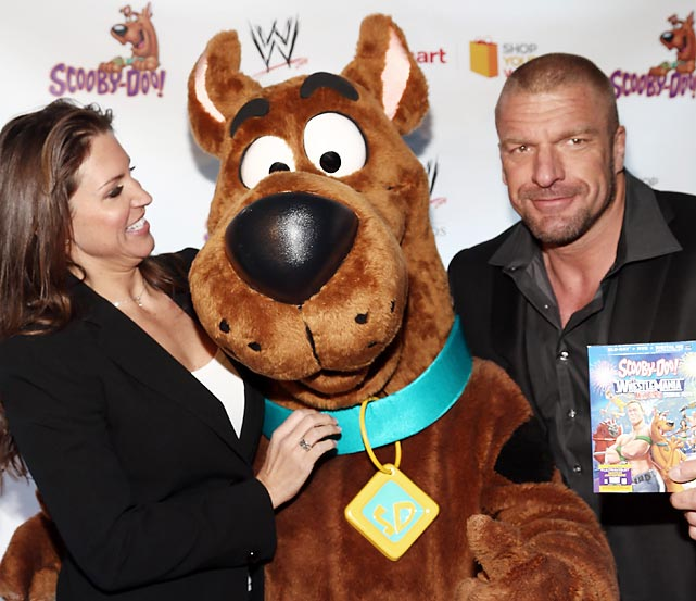 "WWE's Chief Brand Officer collars SI.com's own Scooby Axson at the gala premiere of<italics> Scooby Doo! WrestleMania Mystery</italics> in New York City's Tribeca Cinemas. The animated flick featuring Triple H (the smirking gent on the right) and others of his ilk is being hailed as ""a poignant look at the contemporary social scene"" by people who haven't actually seen it, but would surely like you to believe otherwise."