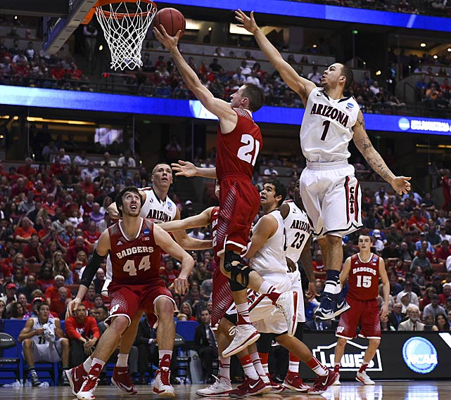 Josh Gasser scores two of his five points as Nick Johnson tries to defend. With three seconds remaining in overtime, Gasser drew a charge call against Johnson as the Wildcats were trying to eclipse a 64-63 deficit.