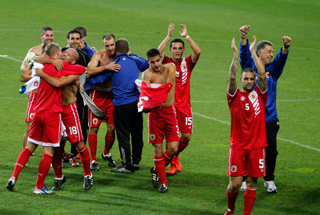 Gibraltar players celebrate after their first game as a member nation of UEFA, a 0-0 draw with Slovakia in Portugal in November 2013.