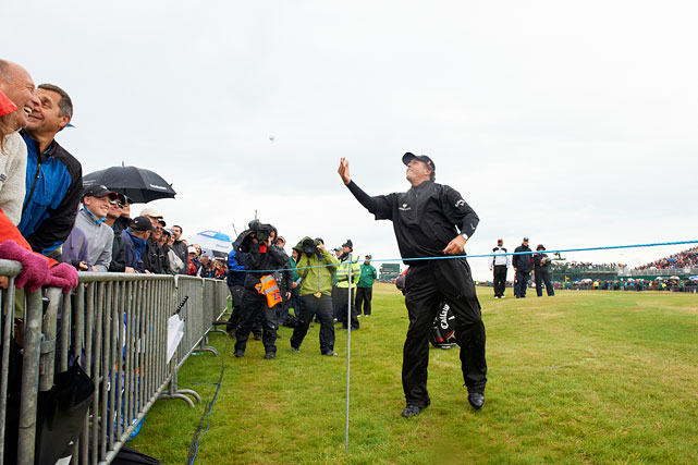 Mickelson tosses a golf ball to a fan in the gallery during the British Open at Royal St. George's GC in Sandwich, England.