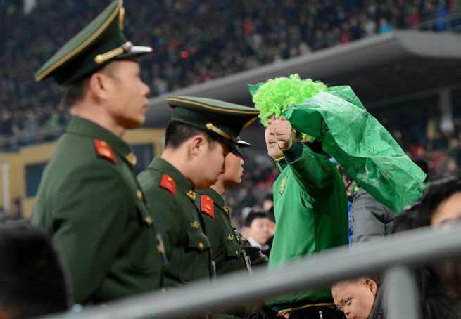 A line of police and security stands between the fans and the field at Beijing Worker's Stadium.