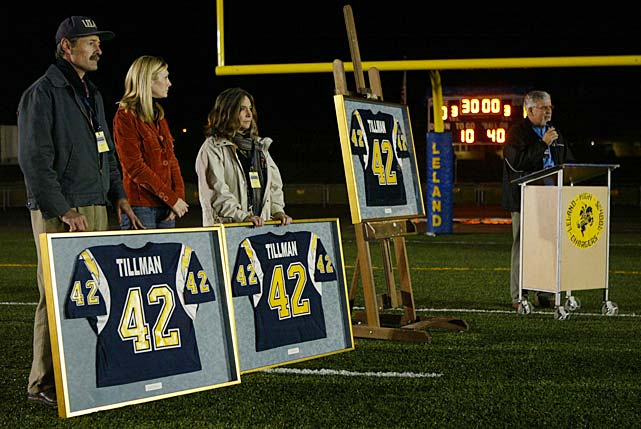 Pat, Marie and Mary Tillman stand next to framed jerseys as Leland (Calif.) High football coach Terry Hardtke speaks at a dedication ceremony in San Jose. Tillman helped Leland to a Central Coast Division I Football Championship. The school retired his jersey and named the new athletic field after him.