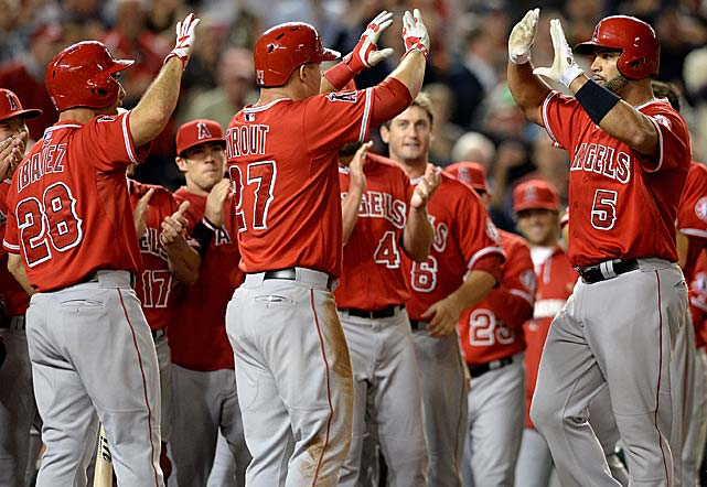 Mike Trout and other teammates greet Pujols after his two-run home run against the Washington Nationals gave him 500 for his career.