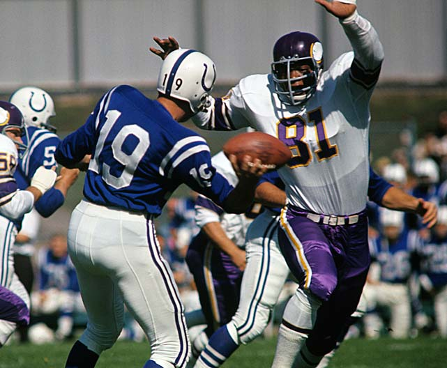 Baltimore Colts quarterback Johnny Unitas faces pressure from Carl Eller of the Minnesota Vikings. Unitas would lead Baltimore to the 1964 NFL Championship, where it would fall to the Cleveland Browns.