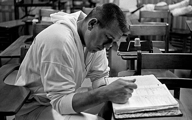 Baltimore Colts quarterback Johnny Unitas studies his playbook.