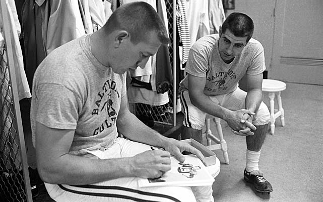 Johnny Unitas signing autographs in the locker room with Earl Morrall before practice at Memorial Stadium. Morrall was the starting quarterback opposite Joe Namath in the 1969 Super Bowl after guiding the Colts to the conference title and winning the league's MVP award.