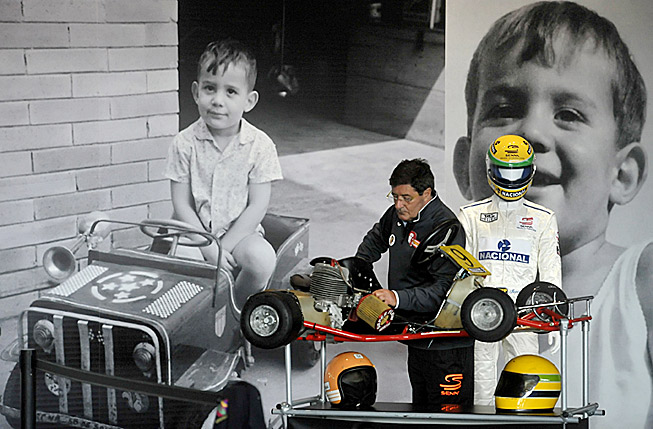 A fan at the track in Imola, Italy is framed by pictures of late F1 driver Ayrton Senna as a boy.