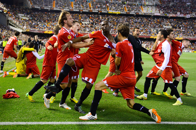 Sevilla players mob Stephane Mbia, center, after his stoppage-time goal put the club in the Europa League final vs. Benfica.