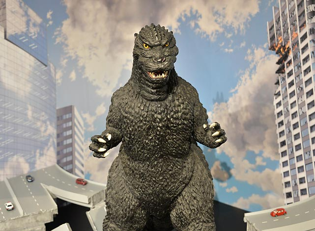 "Japanese fans are beefing about the mean ol' monster that's celebrating its 60th year of pickin' up buses and throwin' 'em back down, and starring in a Hollywood reboot of the post-war sci-fi classic. They say his recent incarnation is too fat and has been ""super-sized"" by an America used to ingesting large portions of grub. Basically, the <italics>New York Post</italics> feels the same way about the fellow in the next frame."