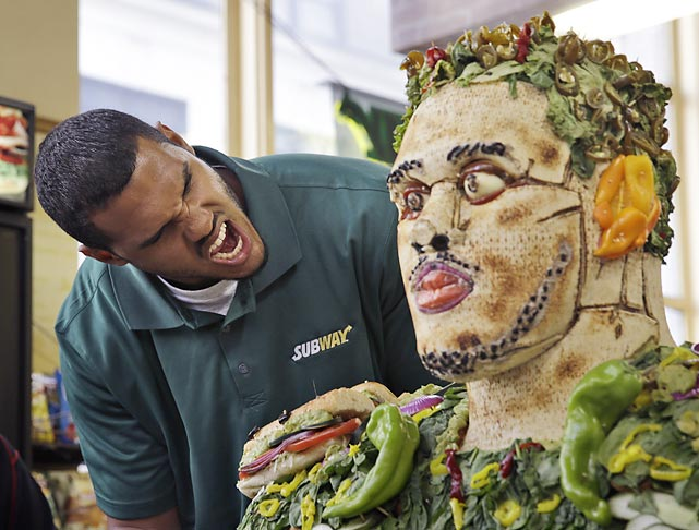 Anthony Barr pretends to eat a sculpture of himself made of food at a Subway restaurant in New York.