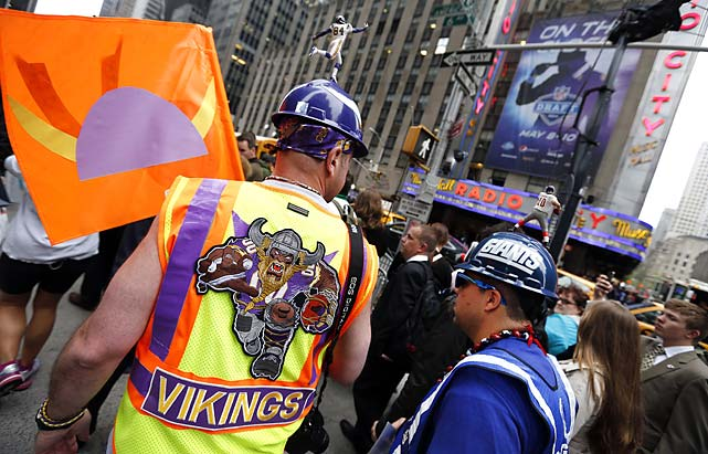 Minnesota Vikings fan John Maranzana, left, of Monticello, N.Y., and New York Giants fan Eric Mabee, of Middletown, N.Y., walk in front of Radio City Music Hall.