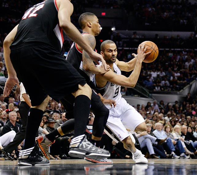 San Antonio Spurs guard Tony Parker drives to the rim against Damian Lillard and Robin Lopez (42) of the Portland Trail Blazers in Game 2 of a Western Conference semifinal.