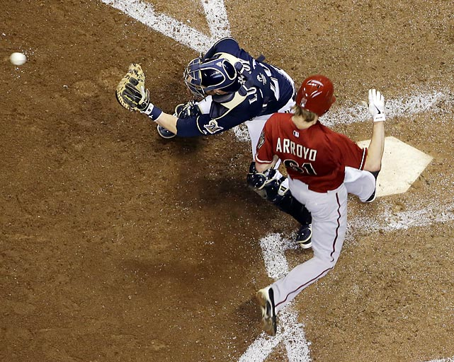 Arizona Diamondbacks pitcher Bronson Arroyo beats a throw to the plate and avoids Milwaukee Brewers catcher Jonathan Lucroy.