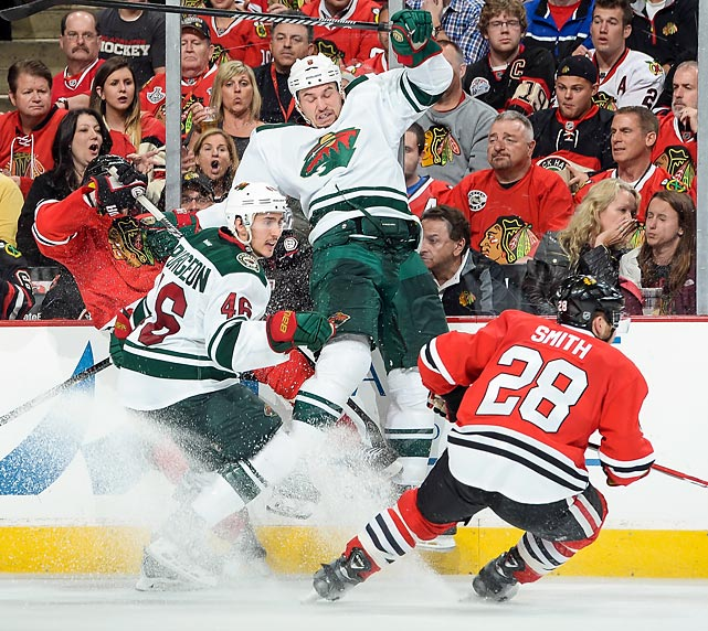 Cody McCormick (center) of the Minnesota Wild slams into the boards behind teammate Jared Spurgeon and Ben Smith of the Chicago Blackhawks in Game 5 of their second-round playoff series.