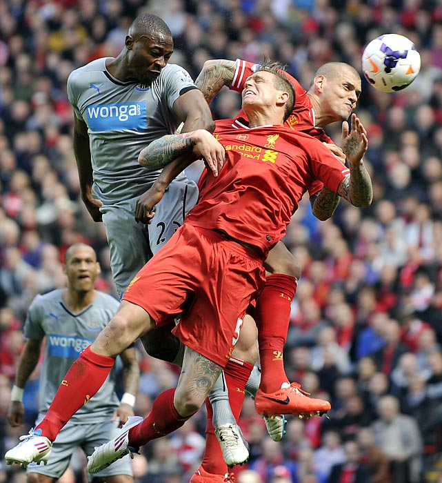 Liverpool's Daniel Agger (center) and Martin Skrtel jockey for the ball against Newcastle United's Shola Ameobi.