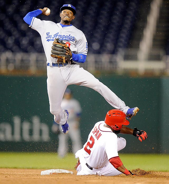 Dee Gordon of the Los Angeles Dodgers leaps over Denard Span of the Washington Nationals to turn a double play.