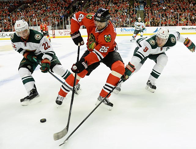 Michal Handzus of the Chicago Blackhawks fights off Nino Niederreiter (left) and Mikko Koivu of the Minnesota Wild for a loose puck in Game 5 of their second-round series.