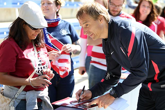 Klinsmann signs an autograph at a public U.S. national team practice in 2012.