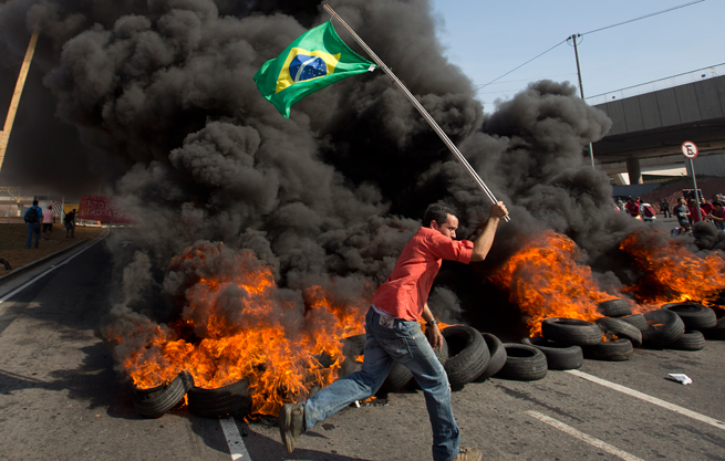 A member of the Homeless Workers Movement runs by burning rubber carrying the Brazilian flag outside of Itaquerao Stadium in Sao Paulo.