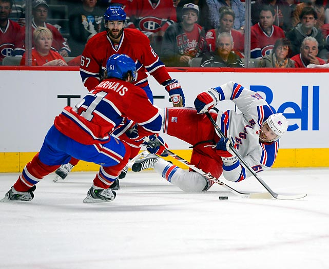 Rick Nash of the New York Rangers gets tripped up by Montreal Canadiens defenders.